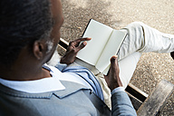 Man reading on bench in a park, partial view - IGGF00090