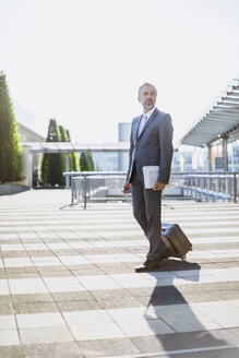 Businessman pulling rolling suitcase outdoors - DIGF02616