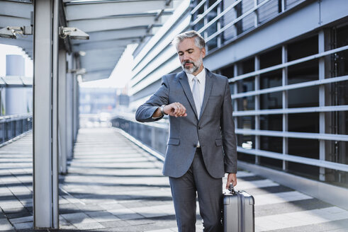 Businessman on a business trip checking the time - DIGF02631