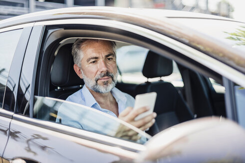 Businessman looking at cell phone in car - DIGF02670