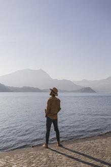Italy, Lierna, man standing at lakeside promenade enjoying sunset - MRAF00216