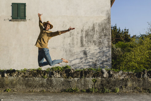 Happy young man jumping in the air - MRAF00219