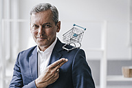 Portrait of manager with mini shopping cart - KNSF02369