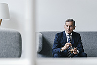 Mature businessman with glass of coffee sitting on couch in his office - KNSF02384