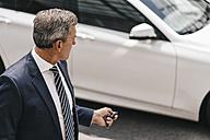 Businessman using remote control key of car - KNSF02390