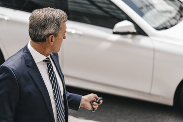 Businessman using remote control key of car - KNSF02390