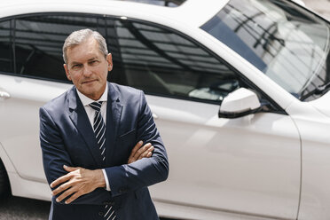 Portrait of mature businessman standing in front of car - KNSF02393
