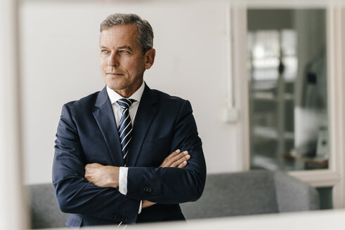 Portrait of mature businessman with arms crossed in his office - KNSF02396