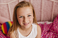 Portrait of smiling little girl in bedroom - NMSF00137