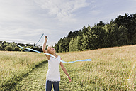 Young girl with gymnastics band on a meadow - NMSF00143