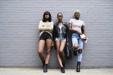 Three friends leaning against grey wall - IGGF00108