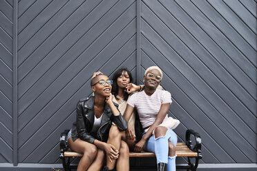 Three friends sitting together on a bench - IGGF00111
