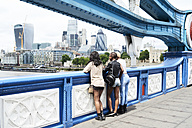UK, London, back view of three friends looking at skyline - IGGF00114