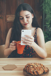 Freckled young woman with coffee mug using smartphone - RTBF00998