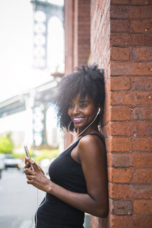 USA, New York City, Brooklyn, smiling woman leaning against brick wall listening to music - GIOF03080