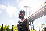 USA, New York City, Brooklyn, smiling woman listening to music at Manhattan Bridge - GIOF03083