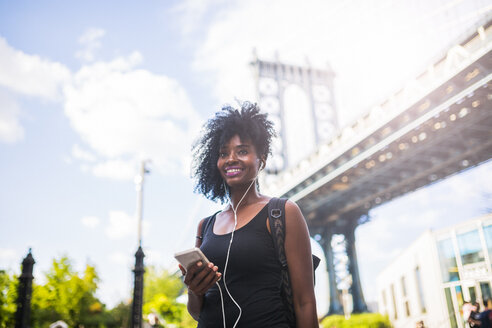 USA, New York City, Brooklyn, smiling woman listening to music at Manhattan Bridge - GIOF03083