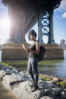 USA, New York City, Brooklyn, woman listening to music under Manhattan Bridge - GIOF03086