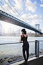 USA, New York City, Brooklyn, woman listening to music near Manhattan Bridge - GIOF03089