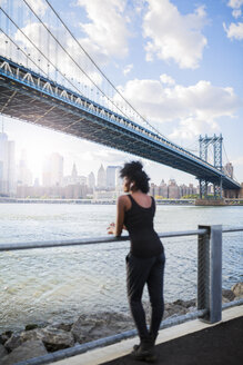 USA, New York City, Brooklyn, woman listening to music near Manhattan Bridge - GIOF03089