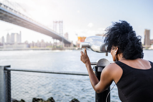 USA, New York City, Brooklyn, woman looking through coin-operated binoculars at Manhattan Bridge - GIOF03092