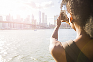 USA, New York City, Brooklyn, woman taking cell phone picture of skyline - GIOF03095