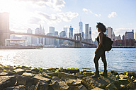 USA, New York City, Brooklyn, woman standing at the waterfront - GIOF03098