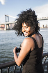 USA, New York City, Brooklyn, portrait of smiling woman standing at the waterfront - GIOF03113