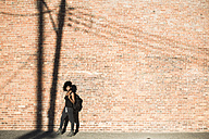 Woman with backpack in front of brick wall with shadow of a power pole - GIOF03116