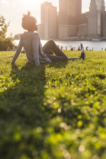 USA, New York City, Brooklyn, woman sitting on meadow looking at the skyline - GIOF03119