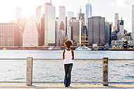 USA, New York City, Brooklyn, woman standing at the waterfront looking at the skyline - GIOF03128