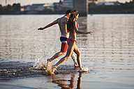 Happy couple running in water - VPIF00017