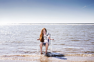 Netherlands, Zandvoort, happy girl sitting on chair in the sea - FMKF04307