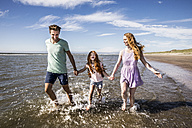 Netherlands, Zandvoort, happy family splashing in the sea - FMKF04313