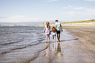 Netherlands, Zandvoort, family walking at the seashore - FMKF04316
