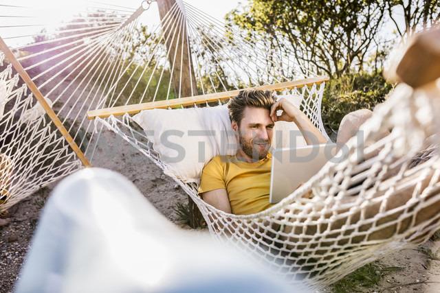 Man lying in hammock using tablet - FMKF04322 - Jo Kirchherr/Westend61
