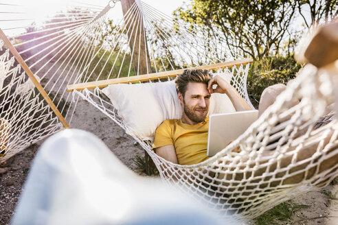 Man lying in hammock using tablet - FMKF04322