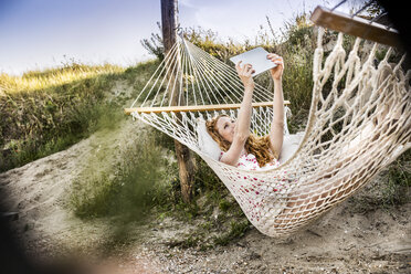 Woman lying in hammock taking a selfie with tablet - FMKF04325