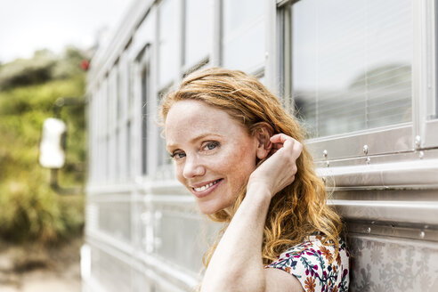 Portrait of smiling woman at an old bus - FMKF04328