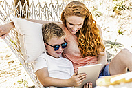 Happy mother and son lying in hammock looking at tablet - FMKF04331