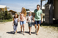 Netherlands, Zandvoort, happy family walking on campsite - FMKF04337