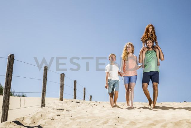 Netherlands, Zandvoort, happy family walking on the beach - FMKF04343