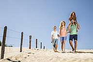 Netherlands, Zandvoort, happy family walking on the beach - FMKF04343