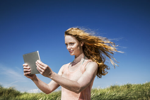 Netherlands, Zandvoort, woman standing in dunes with tablet - FMKF04346