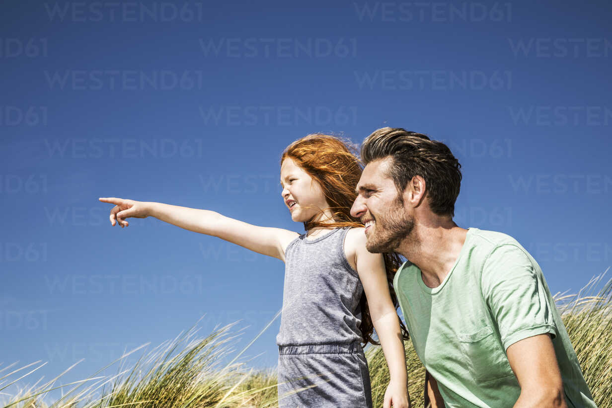 Netherlands, Zandvoort, father and daughter on in beach dunes looking out - FMKF04349 - Jo Kirchherr/Westend61
