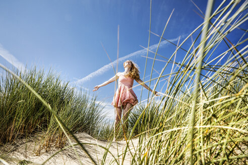 Netherlands, Zandvoort, happy woman standing in dunes with outstretched arms - FMKF04352