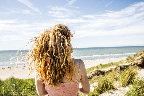 Netherlands, Zandvoort, woman standing in dunes - FMKF04355