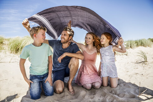 Netherlands, Zandvoort, happy family under a blanket on the beach - FMKF04358