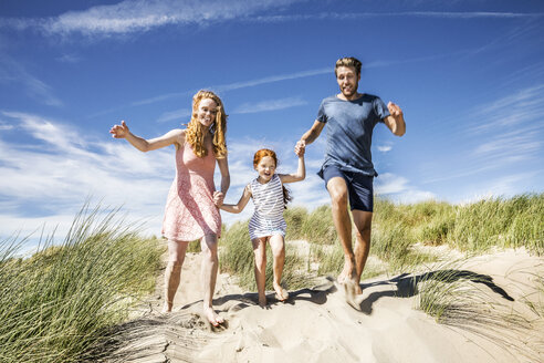 Netherlands, Zandvoort, happy family with daughter running in beach dunes - FMKF04361