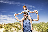 Netherlands, Zandvoort, father carrying daughter on shoulders in beach dunes - FMKF04364